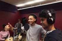 Musicisti adolescenti sorridenti che registrano musica, cantano in cabina sonora — Foto stock