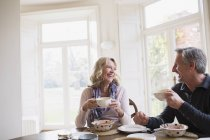 Smiling, happy mature couple eating breakfast, drinking coffee — Stock Photo