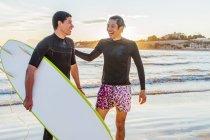 Felizes masculinos surfistas na praia do oceano — Fotografia de Stock