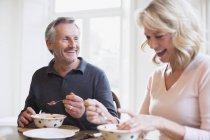Smiling mature couple eating breakfast at modern home — Stock Photo