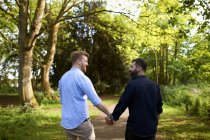 Affectionate male gay couple holding hands in sunny park — Stock Photo