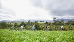 Friends mountain biking in idyllic, remote field — Stock Photo