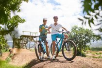 Father and son mountain biking at sunny obstacle course — Stockfoto