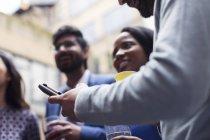 Uomo texting con il telefono astuto alla festa — Foto stock