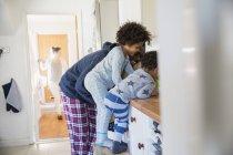 Батько і діти в піжамі в кухонного столу — стокове фото