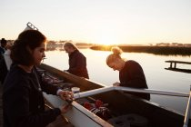 Female rowers preparing scull at sunrise lakeside — Stock Photo
