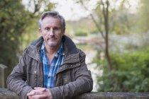 Portrait of confident mature caucasian man in autumn park — Stock Photo