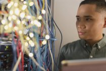 Focused male IT technician examining wires on server panel — Stock Photo