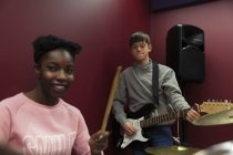 Smiling teenage musicians recording music, singing and playing electric guitar  in sound booth — Stock Photo