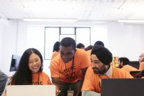 Hackers at laptops coding for charity at hackathon — Stock Photo