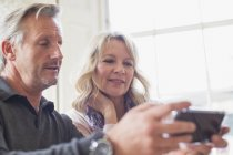 Mature couple using smart phone at modern home — Stock Photo