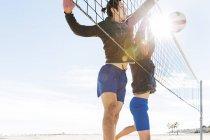 Hombres jugando voleibol de playa en la playa soleada - foto de stock