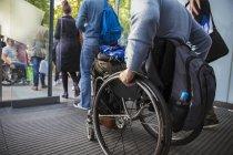 Image recadrée de l'homme en fauteuil roulant quittant le bureau — Photo de stock