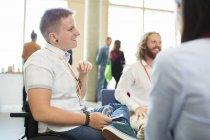 Улыбающаяся женщина в инвалидной коляске разговаривает с коллегами на конференции — стоковое фото