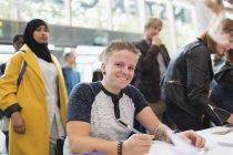 Улыбающаяся женщина в инвалидной коляске регистрируется за регистрационным столом конференции — стоковое фото