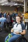 Портрет улыбающейся, уверенной в себе молодой женщины в инвалидной коляске, пьющей кофе на конференции — стоковое фото