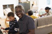 Портрет счастливой дед, играть на фортепиано с внуком — стоковое фото