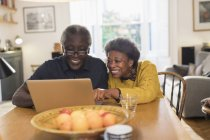 Senior couple using laptop at dining table — Stock Photo