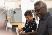 Дідусь і онук, грати на фортепіано вдома — стокове фото