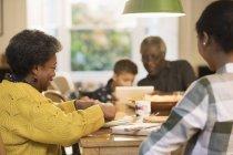 Сім'я їсть і використовуючи цифровий планшетний обіднім столом — стокове фото