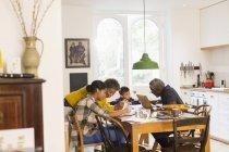 Бабусі і дідусі, допомагаючи онуків з домашнє завдання в обідній стіл — стокове фото