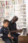 Дідусь і онук гри фортепіано та кларнет — стокове фото