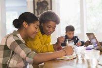 Großmutter hilft Enkelin bei Hausaufgaben — Stockfoto