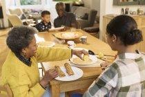 Бабушка и внучка, едят блины обеденным столом — стоковое фото