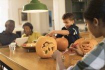Großeltern mit Enkeln Halloween Kürbisse schnitzen zu Tisch — Stockfoto
