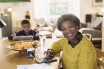 Retrato, sorrindo pagando contas de mulher sênior na mesa de jantar — Fotografia de Stock