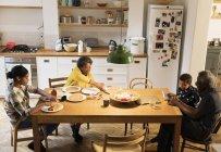 Бабушки и внуки едят и используют цифровые планшеты за обеденным столом — стоковое фото