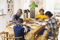 Grandparents at dining table with grandchildren doing homework — Stock Photo