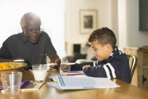 Grandfather at table with grandson doing homework — Stock Photo