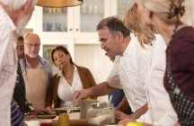 Chef explaining to active senior friends in cooking class — Stock Photo