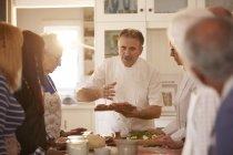 Senioren Freunde anhören Koch in Pizza Kochkurs — Stockfoto