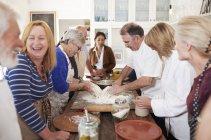 Senior friends enjoying pizza cooking class, making dough — Stock Photo