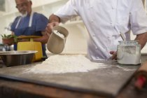 Close up chef pouring water into pizza dough flour nest in cooking class — Stock Photo