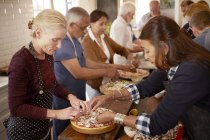 Senior women friends making pizza in cooking class — Stock Photo