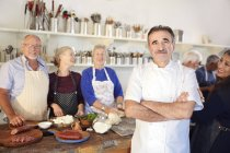 Portrait confident chef with senior students in cooking class kitchen — Stock Photo