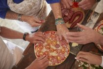 Overhead view senior friends adding tomatoes and meat to fresh pizza — Stock Photo