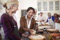Amis de femmes âgées râper le fromage sur la pizza en cours de cuisine — Photo de stock