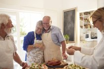 Affectionate senior couple enjoying pizza cooking class — Stock Photo