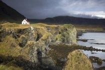 Casa alejada en acantilado escarpado y remoto, Arnarstapi, Snaefellsnes, Islandia - foto de stock
