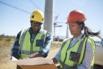 Инженеры просматривают чертежи на электростанции — стоковое фото