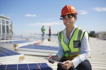 Portrait smiling, confident female engineer with digital tablet inspecting solar panels at sunny power plant — Stock Photo
