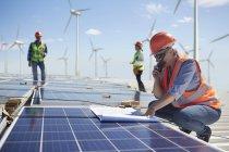 Ingenieur mit Walkie-talkie und Blueprint bei Solar-Panel im sonnigen Kraftwerk — Stockfoto