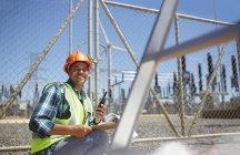 Улыбающийся, уверенный в себе мужчина-инженер с рацией на электростанции — стоковое фото