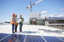 Ingenieure mit Blaupause auf Solar-Panels im sonnigen Kraftwerk — Stockfoto