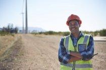 Портрет улыбающегося инженера на грунтовой дороге на ветряной электростанции — стоковое фото