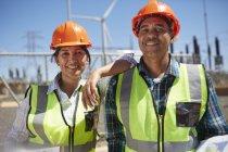 Уверенные в себе портреты, улыбающиеся инженеры на электростанции — стоковое фото